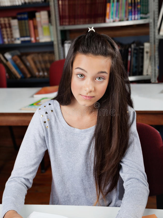 Portrait Of Female Student Sitting In Library royalty free stock image