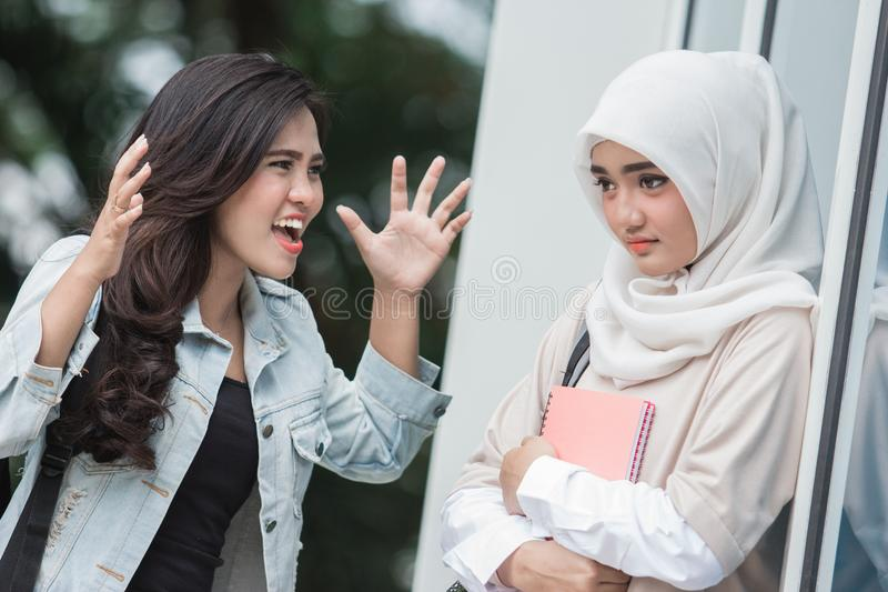Female student bullying. Portrait of female student yelling at her friend on campus or school. bullying concept stock image