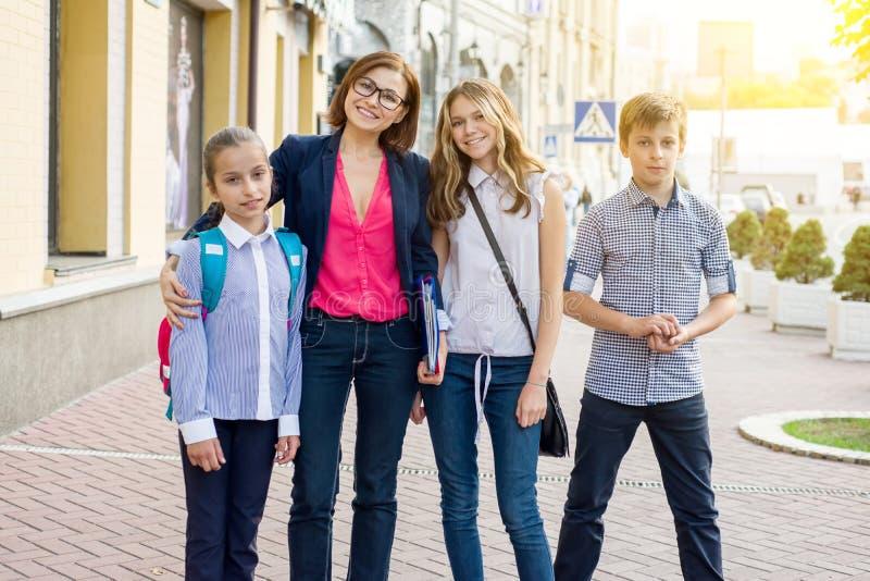 Portrait female teacher with children standing outside school stock photography