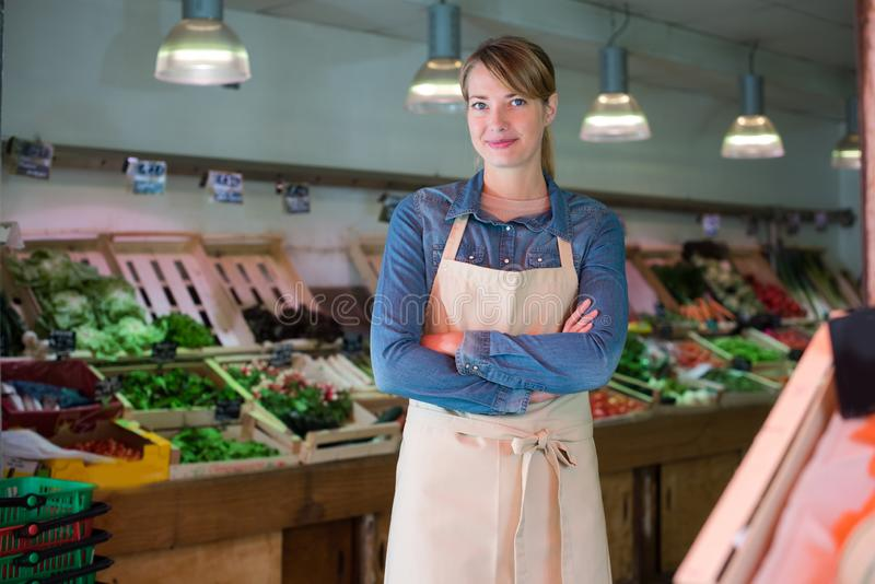 Portrait female worker in green grocers stock photography