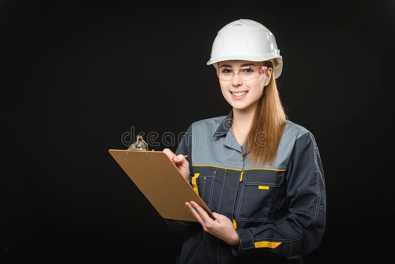 Portrait of a female worker. Portrait of a young female worker on the black background stock photo