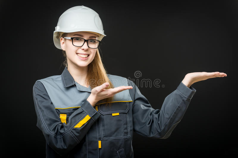 Portrait of a female worker. Portrait of a young female worker on the black background stock photos