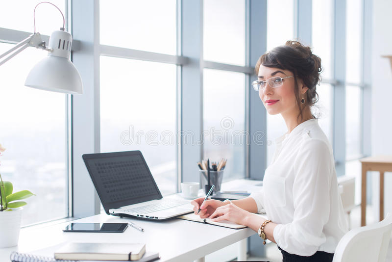 Portrait of a female writer working at office, using laptop, wearing glasses. Young employee planning her work day. Writing in notebook royalty free stock photo