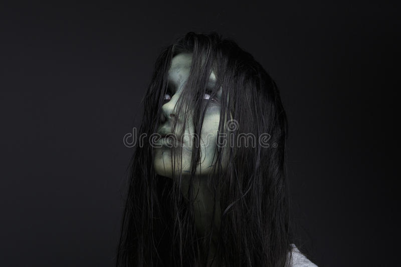 Portrait of a female zombie. Close up portrait of a female zombie on black background stock photography