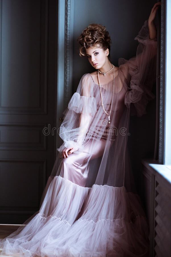 Portrait femelle à la mode de dame mignonne dans la robe rose à l'intérieur images libres de droits