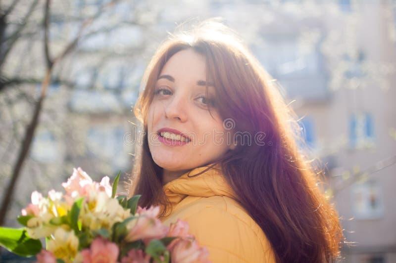Portrait femelle d'extérieur de fille attirante de brune dans la guêpe tenant un grand bouquet d'apprécier coloré de fleurs images stock