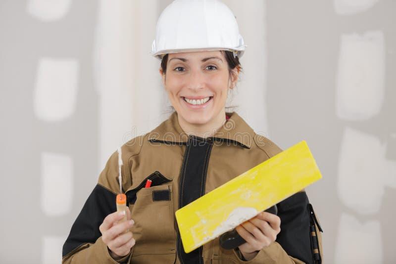Portrait femelle de peintre de plâtrier à la rénovation d'intérieur de mur photographie stock libre de droits