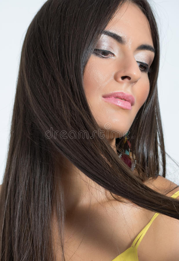 Portrait of feminine woman holding her brown hair lock royalty free stock images