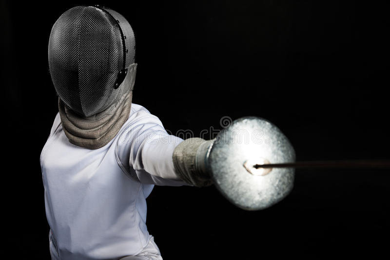 Portrait of fencer woman wearing white fencing costume practicing with the sword. Isolated on black background. stock photo