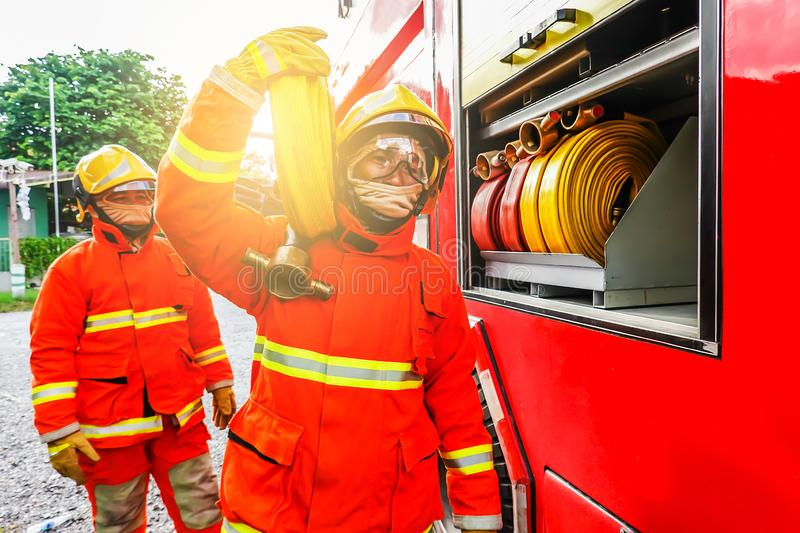 Portrait of a firefighter carrying fire hose on shoulder royalty free stock photos