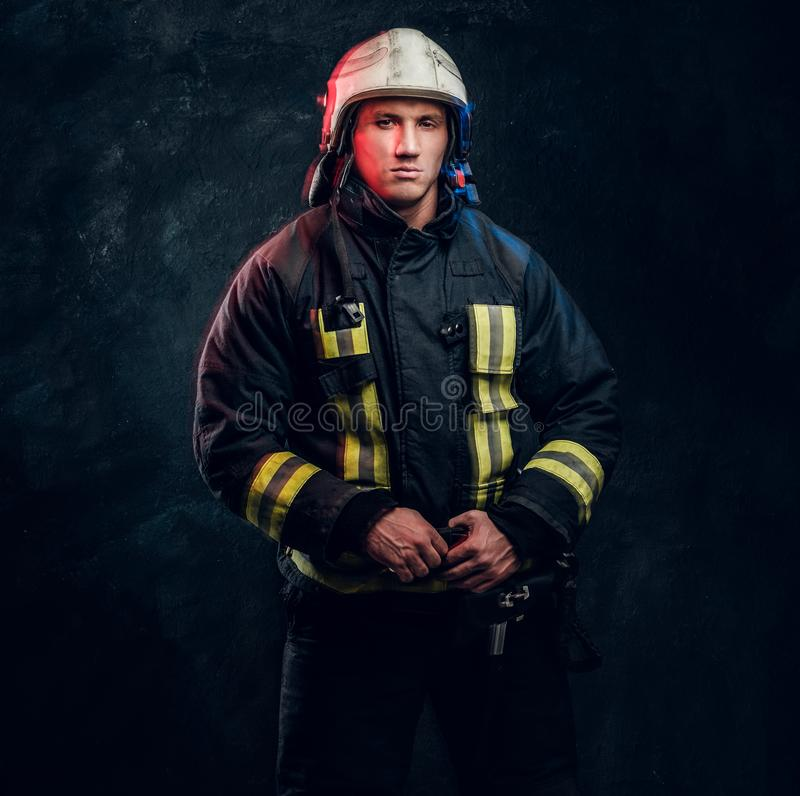 Portrait of firefighter dressed in uniform and safety helmet looking sideways with a confident look royalty free stock photos
