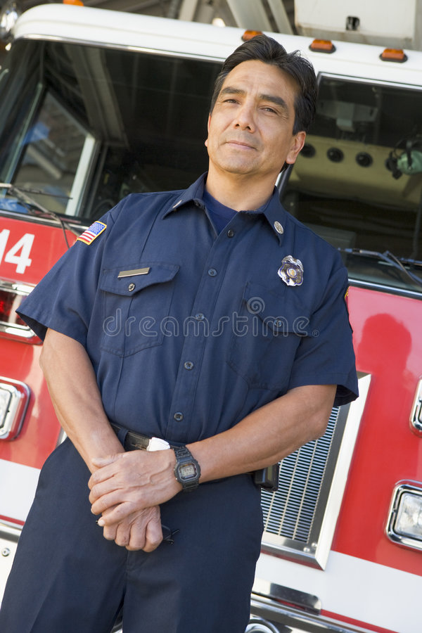 Portrait of a firefighter by a fire engine.  stock images