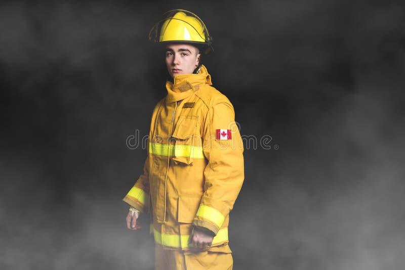 Portrait of the fireman standing Waist up studio shot on black background and moke. stock photography