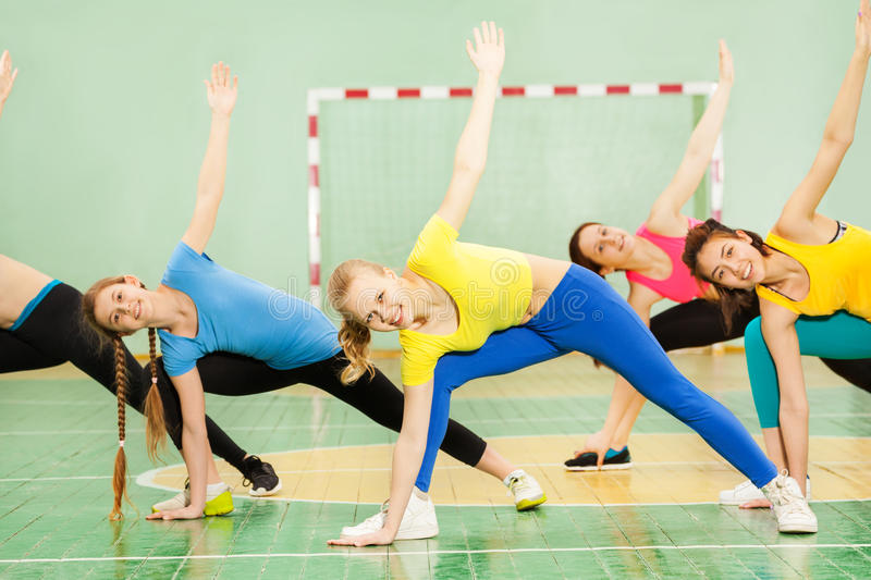 Portrait of fit girls doing exercise in sport gym stock image