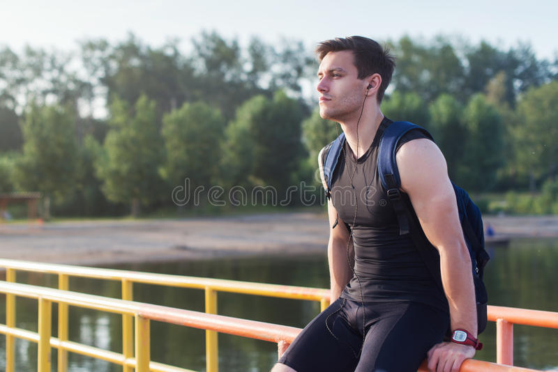 Portrait of fit man runner sitting and resting outdoors near river. stock photography