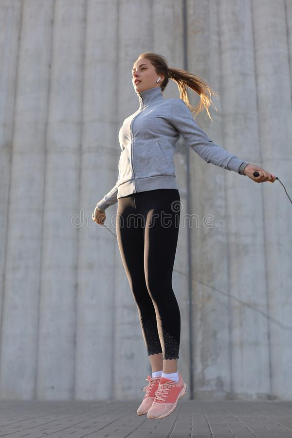 Portrait of fit young woman with jump rope outdoors. Fitness female doing skipping workout outdoors on sunrise or sunset royalty free stock image