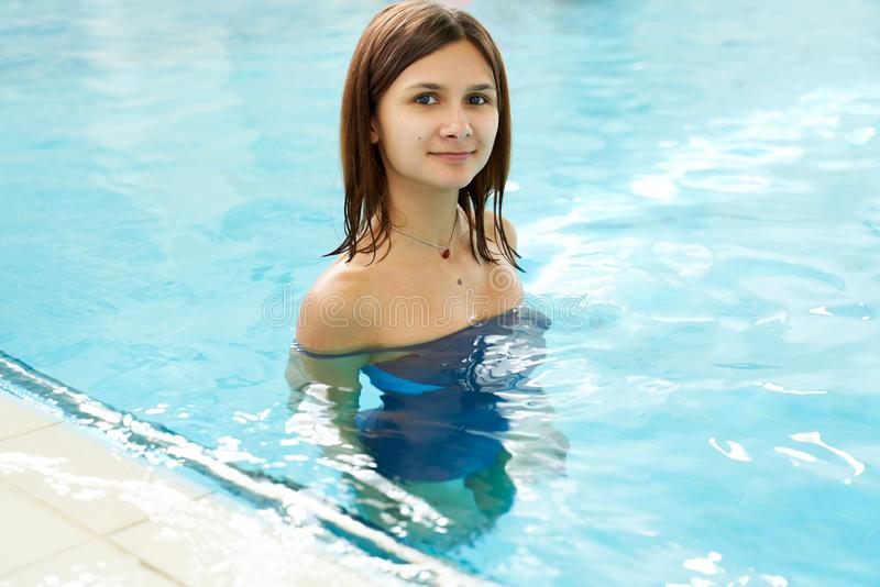 Portrait of a fit young woman in the swimming pool. Happy smiling swimmer female in the pool while training. stock photography