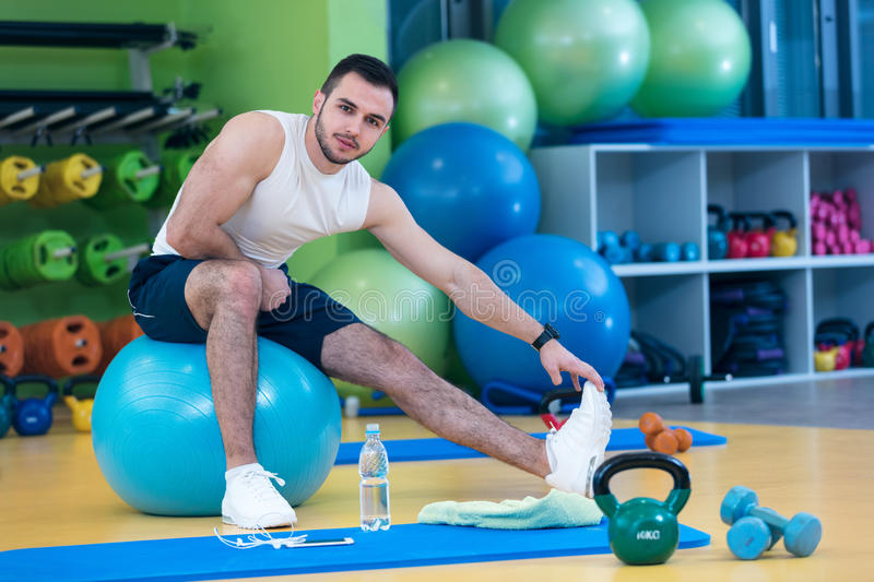 Portrait of a fitness man doing stretching exercises at gym royalty free stock images