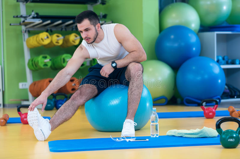 Portrait of a fitness man doing stretching exercises at gym stock photography