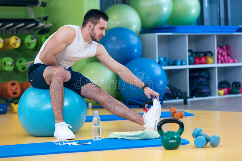 Portrait of a fitness man doing stretching exercises at gym stock image