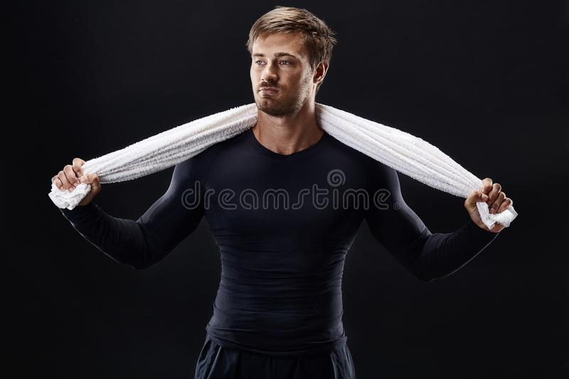 Portrait of a fitness man with towel on shoulders looking away. Happy young man relaxing after training. stock photos