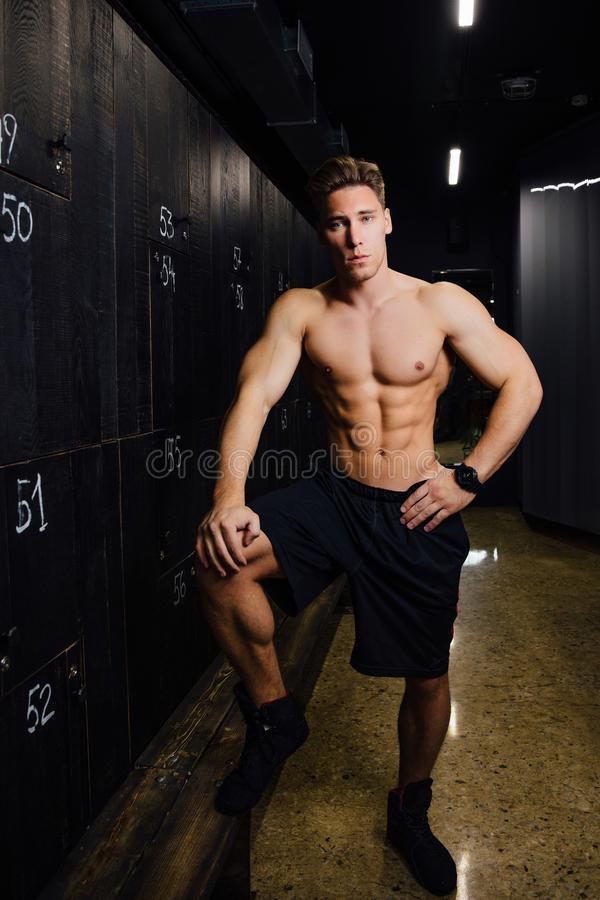 Portrait of fitness model handsome man , torso in locker room. Portrait before or after workout. royalty free stock photo