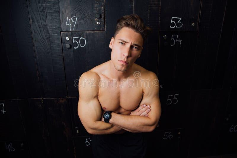 Portrait of fitness model handsome man , torso in locker room. Portrait before or after workout. stock images