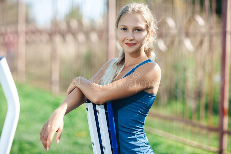 Portrait of fitness young woman in a blue shirt using outdoor gym equipment in the park looking at camera and smiling. stock photos