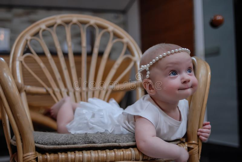 A portrait of a five-month baby girl with clear blue eyes in a white dress and pearly headband. royalty free stock image