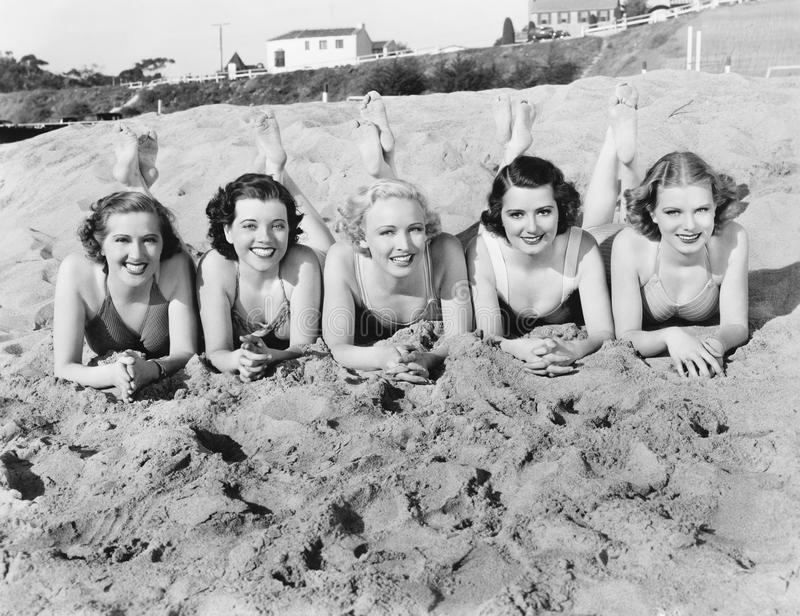 Portrait of five young women lying on the beach and smiling stock photos
