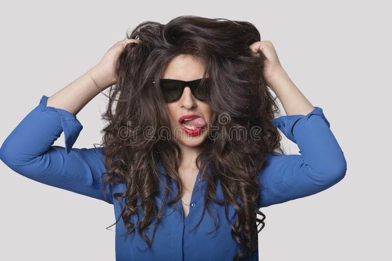 Portrait of a flirtatious young woman over gray background stock photos