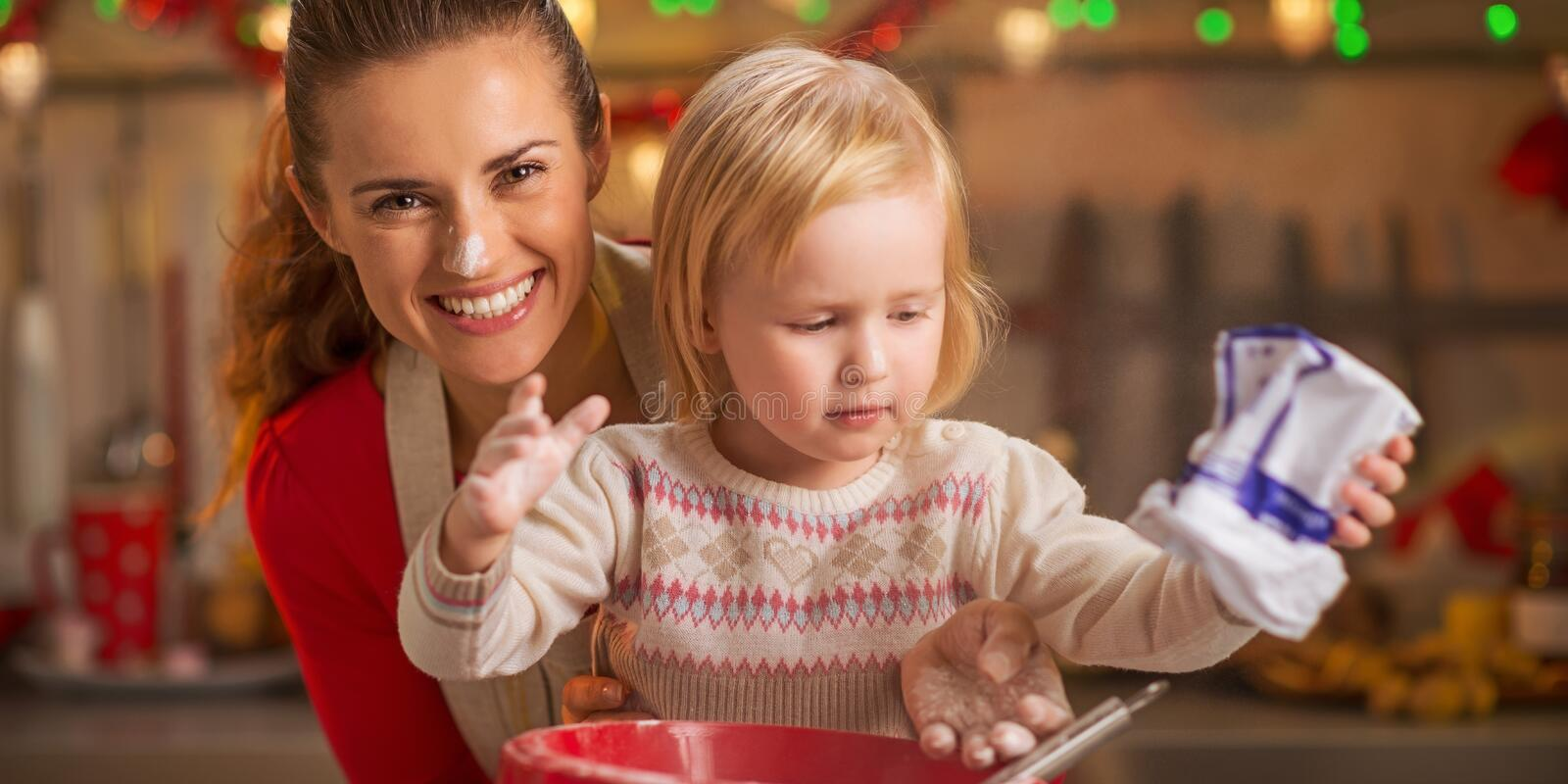 Portrait of flour smeared mother and baby making cookies stock photo