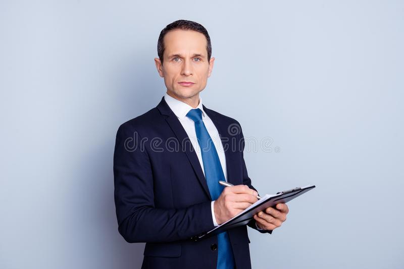 Portrait of focused clever intelligent concentrated representative with pencil and clipboard writing ideas checking work of staff royalty free stock photography