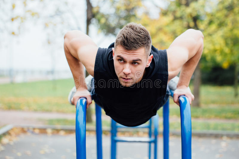 Portrait of focused muscular young man in black workout clothes doing dips on parallel bars. stock photos