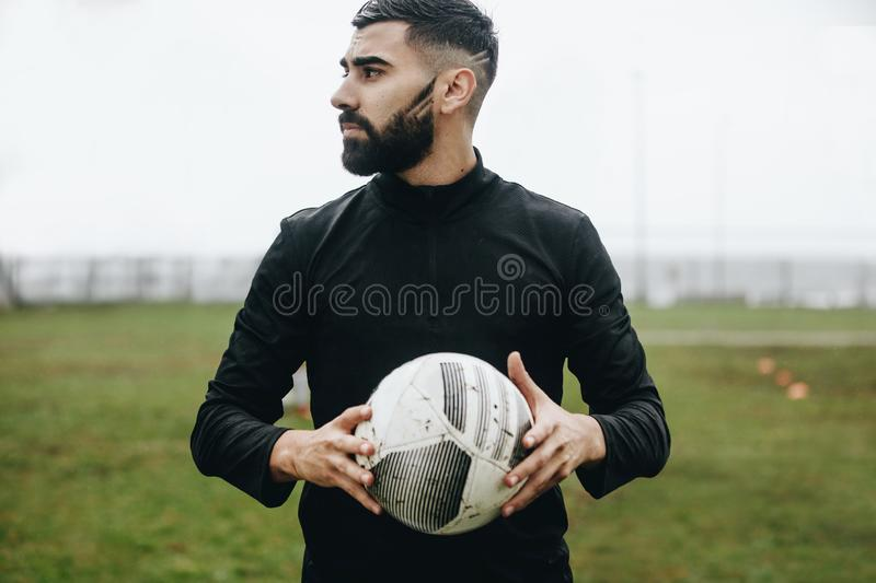 Portrait of a football player standing on field holding a ball looking away. Soccer player standing on ground holding a football. During practice stock images