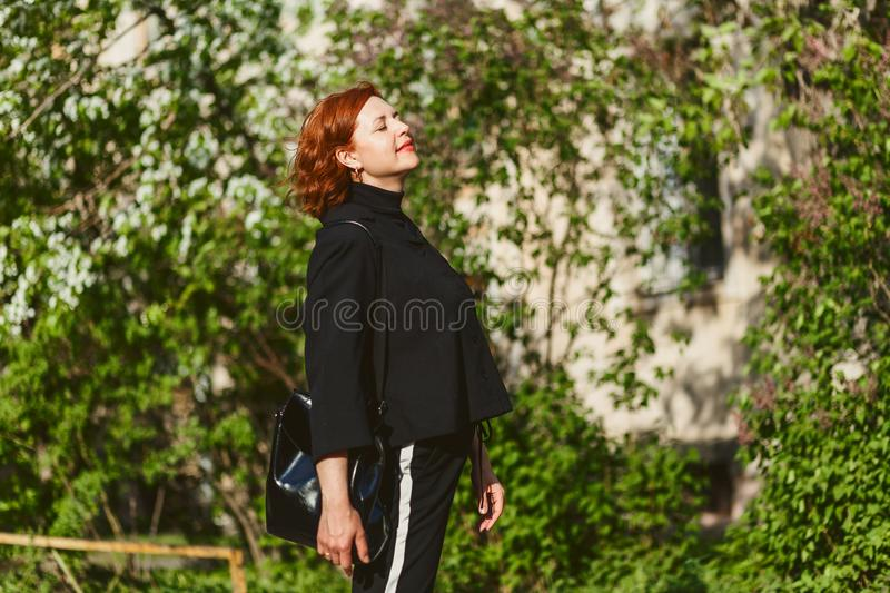 Portrait of forty-year-old red-haired woman in profile outdoors stock photos