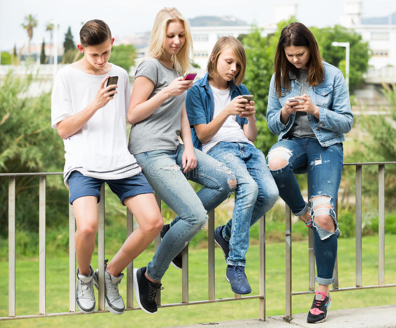 Portrait of four teenagers sitting with their mobile phones outdoors royalty free stock photos