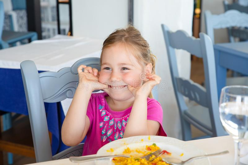 Little girl making fun with paella dish in restaurant royalty free stock image