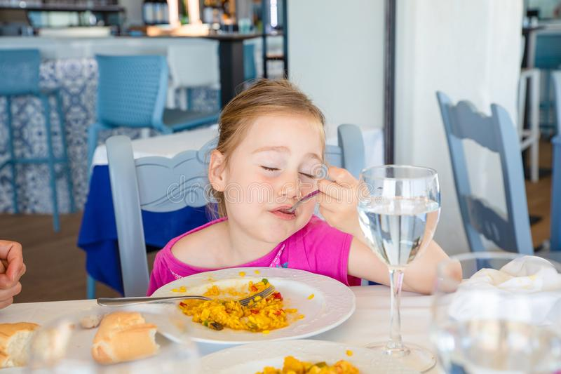 Little girl eating paella with satisfaction expression. Portrait of four years old blonde girl eating Spanish paella rice from white plate, with satisfaction royalty free stock photography