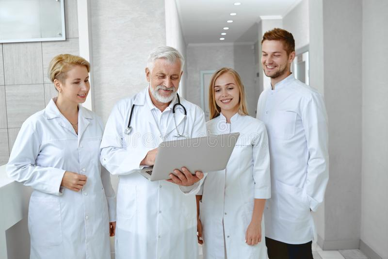 Portrait of fout doctors talking in white uniform. stock photography