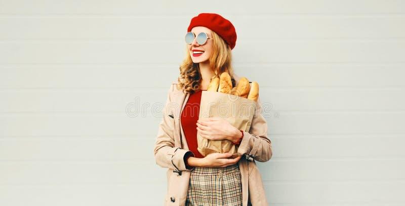 Portrait fröhliche junge lächelnde Frau halten Einkaufstasche mit langen weißen Brot Baguette mit Blick weg lizenzfreie stockfotos