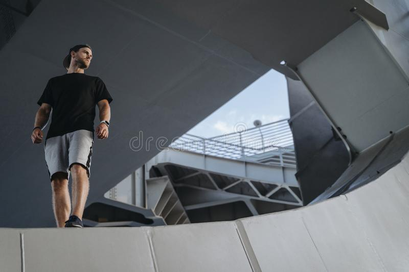 Portrait of freerunning athlete standing on the edge. Metal construction. Looking at place for your advertise royalty free stock image
