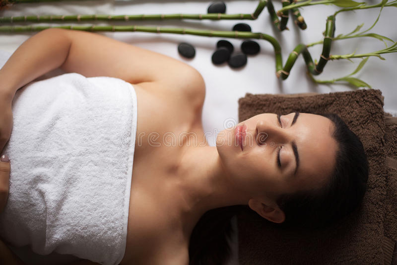 Portrait of fresh and beautiful brunette woman taking head massage stock image