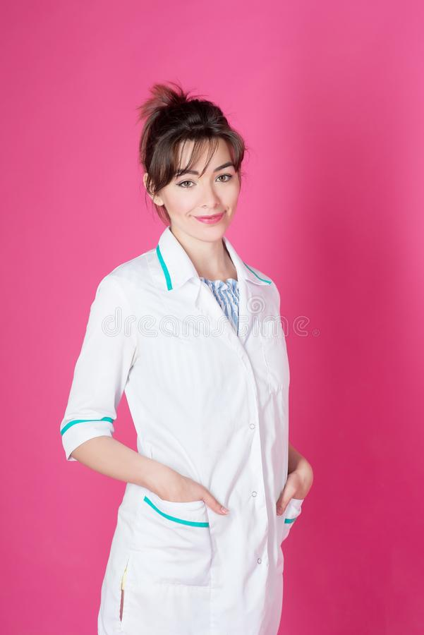 Portrait of friendly doctor cosmetologist, beautication, cosmetition on pink background. stock photos