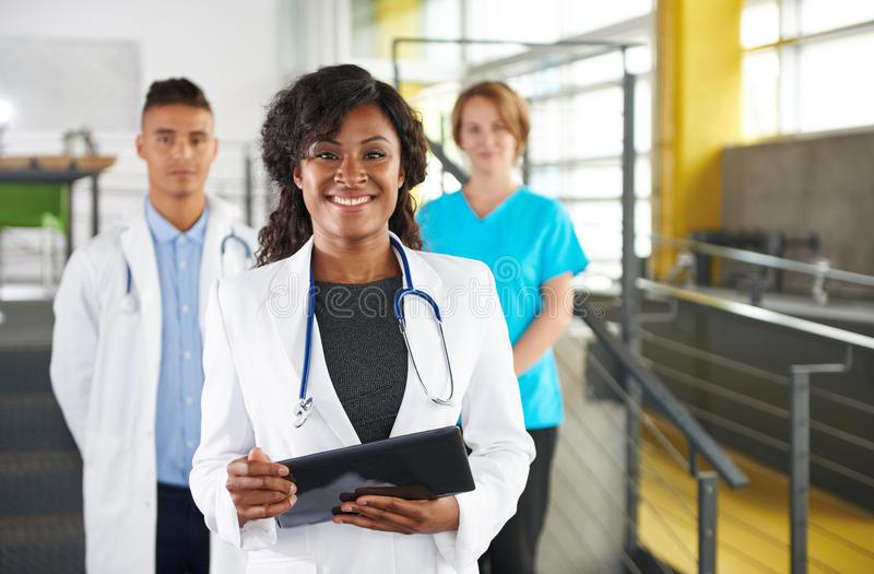 Portrait of a friendly female african american doctor and team in bright modern office royalty free stock image