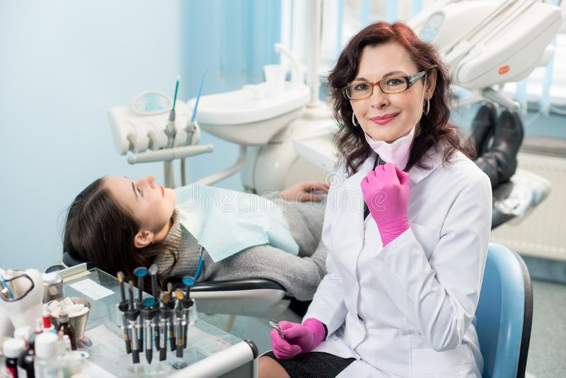 Portrait of friendly female dentist with patient in the chair at the dental office royalty free stock photography