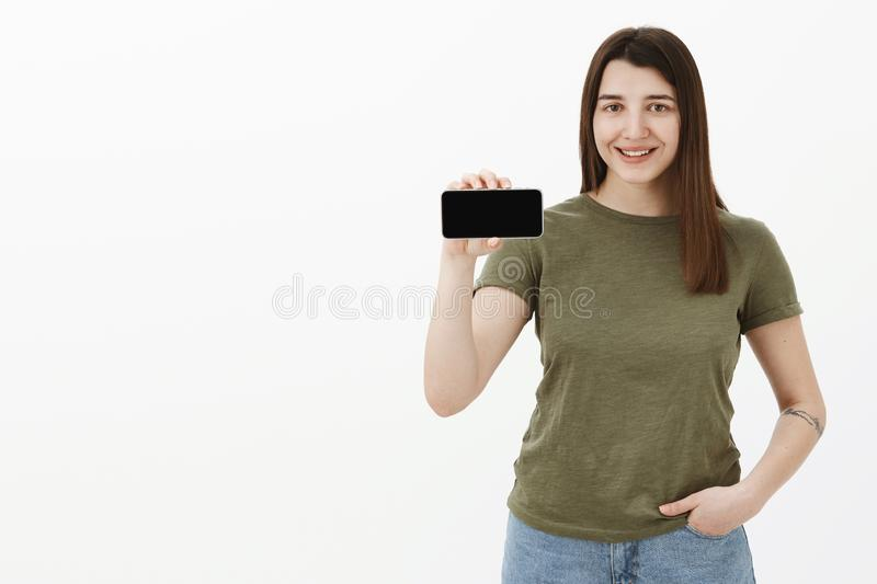 Portrait of friendly and happy young pleased positive brunette in casual t-shirt smiling and showing smartphone in. Horizontal position as presenting app or royalty free stock photo