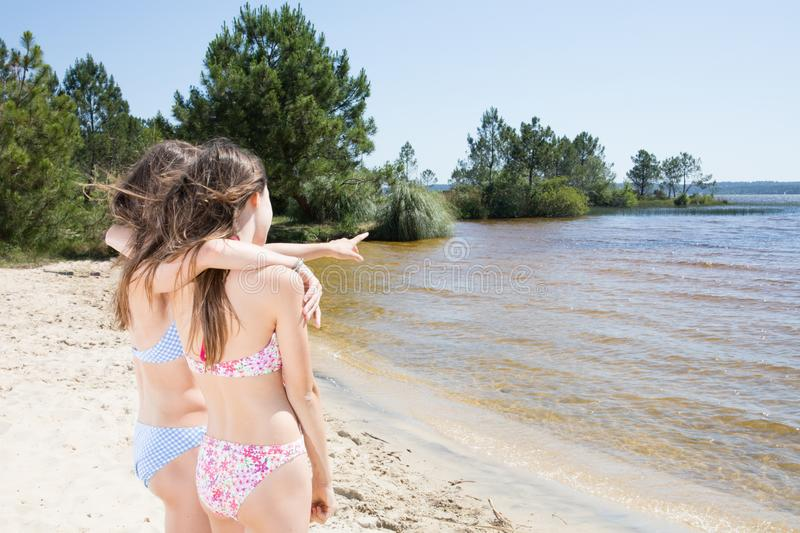 Portrait of friends beautiful happy girl on sea and spraying at the beach stock photography