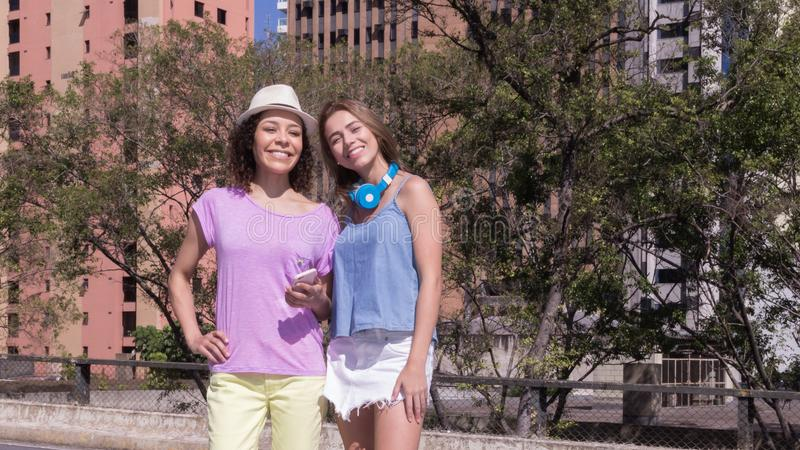 Portrait of friends with colorful clothes and hat in the streets. Bright day. Portrait of Mixed race friends with colorful clothes and hat in the streets of the royalty free stock photos
