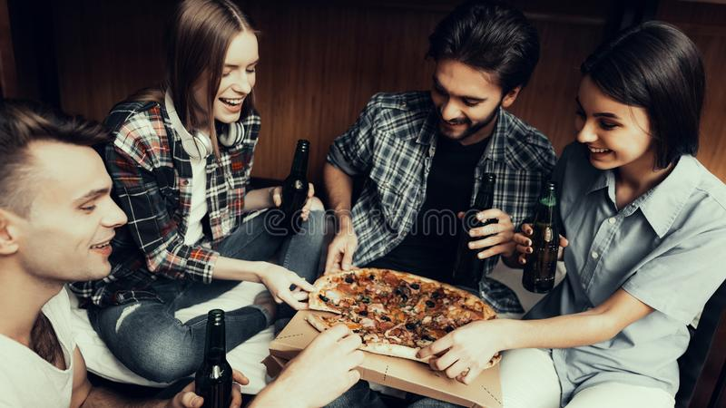 Portrait of Friends relaxing Together, eat Pizza. Hostel for Young People. Best Friends Traveling. Small Room in Hostel. spend time Together. smiling People royalty free stock image